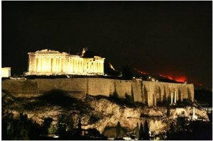 Flames illuminate the ridge behind the Acropolis